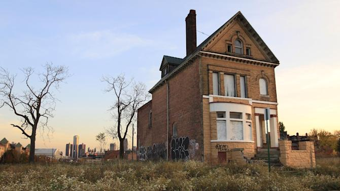 FILE - This Oct. 24, 2012 file photo shows a graffiti-marked abandoned home north of downtown Detroit, in background. A state-appointed review team Tuesday, Feb. 19, 2013 determined Detroit is in a financial emergency, paving the way for Republican Gov. Rick Snyder to appoint an emergency manager who would need to come up with a new plan to get the city out of its fiscal crisis.   (AP Photo/Carlos Osorio, File)