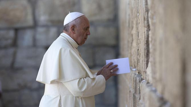 Pope Francis places an envelope in on of the cracks between the stones of the Western Wall, the holiest place where Jews can pray, in the Old City of Jerusalem, Israel, Monday, May 26, 2014. (AP Photo/Andrew Medichini, Pool)