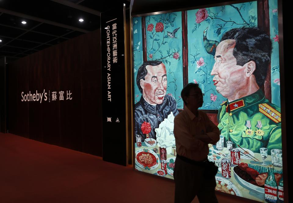 "A man walks past a poster of a painting ""Revolutionary Family Series – Invitation to Dinner"" by Chinese artist Liu Wei at the Sotheby's autumn auction in Hong Kong Monday, Oct. 8, 2012. The work sold for US$2.24 million set a world auction record for the artist. (AP Photo/Vincent Yu)"