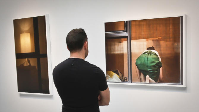A visitor views the photography of Arne Svenson on Thursday, May 16, 2013 at the Julie Saul Gallery in New York.  Residents of a New York luxury apartment building are upset over the exhibition by Svenson who  secretly made their pictures from his window across the street. (AP Photo/Bebeto Matthews)