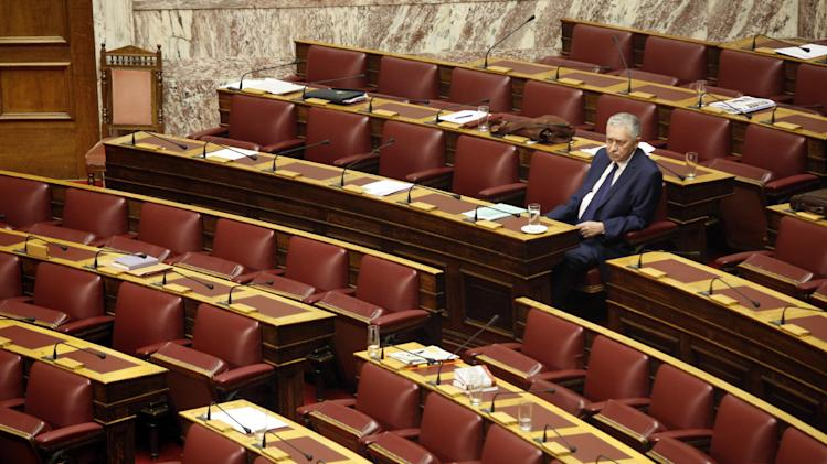 Greek leader of the Left Democratic party, Dimar,  Fotis Kouvelis sits among empty seats while awaiting for his turn to speak at the Parliament in Athens, Saturday, July 7, 2012. Greeces' left party lawmakers  left the parliament hall during Nikolaos Michaloliakos' speech. ( AP Photo/Kostas Tsironis)