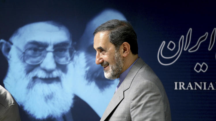 Iranian presidential candidate Ali Akbar Velayati, a former Foreign Minister, walks past a portrait of supreme leader Ayatollah Ali Khamenei at the conclusion of his press conference in Tehran, Iran, Monday, June 3, 2013. The 11th presidential election after Iran's 1979 Islamic Revolution will be held on June 14. (AP Photo/Ebrahim Noroozi)