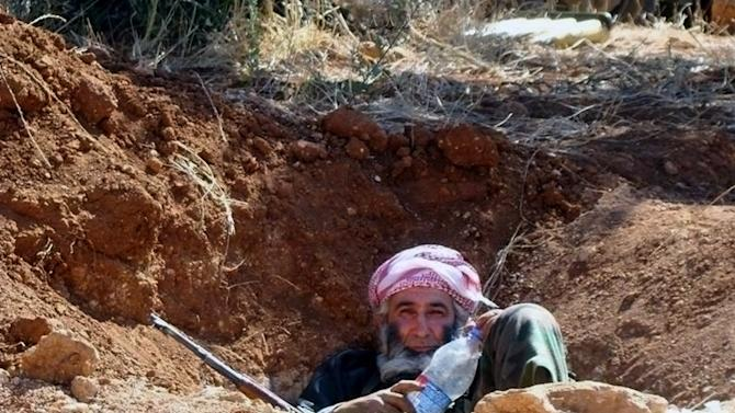 """This citizen journalism image provided by Edlib News Network, ENN, which has been authenticated based on its contents and other AP reporting, shows an elderly Syrian rebel sit in a trench, in Idlib province, northern Syria, Wednesday, June 12, 2013. Syrian rebels have attacked a village in the country's east, killing dozens of Shiites, mostly pro-government fighters, activists said Wednesday. A Syrian government official denounced the attack, saying it was a """"massacre"""" of civilians. (AP Photo/Edlib News Network ENN)"""