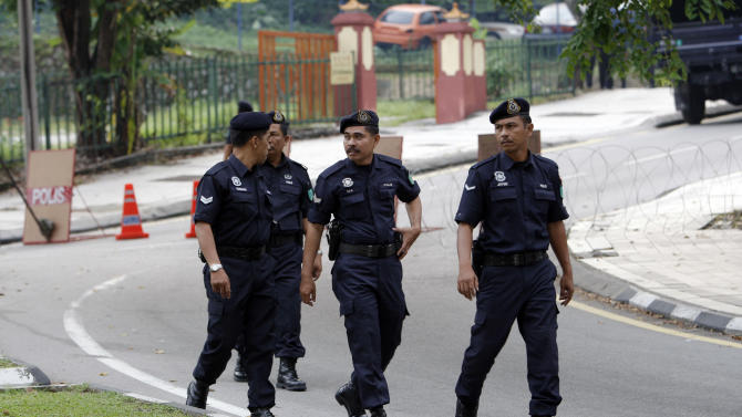 Malaysian police officers walk near a main road in city center of Kuala Lumpur, Malaysia, Saturday, July 9, 2011. Malaysian police said Friday, they would shut major roads and suspend public transportation into Kuala Lumpur's city center to thwart opposition-backed activists, who vowed Friday to press ahead with a banned rally for electoral reforms. (AP Photo/Vincent Thian)