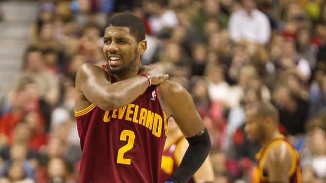 Cleveland Cavaliers' Kyrie Irving massages his shoulder after injuring it in a fall during second half NBA basketball action against Toronto Raptors' in Toronto on Sunday March 10 , 2013. (AP Photo/The Canadian  Press, Chris Young)