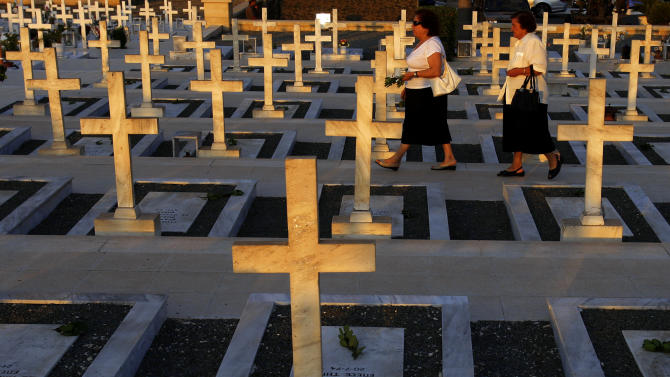 Two women walk by the graves of Greek and Cypriot soldiers who were killed in the 1974 Turkish invasion of Cyprus at the Tymvos Macedonitissas military cemetery in the divided capital of Nicosia, Cyprus, Tuesday, July 19, 2011. Greek and Cypriot soldiers were killed in 1974 during the Turkish invasion and subsequent occupation of the northern part of the island of Cyprus. July 20, is 37th anniversary of Turkish invasion. Cyprus was split into Greek Cypriot south and Turkish Cypriot north in 1974 when Turkey invaded in response to a coup by supporters of union with Greece. (AP Photo/Petros Karadjias)
