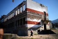 A Roma woman walks by the building of the old school of Berkovitsa in August 2012. According to last year's census, a massive 12 percent of the Roma minority is illiterate, compared to 0.5 percent for the rest of the population