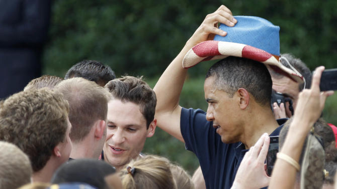 President Barack Obama puts on a red, white, and blue hat, while visiting with service members during the Independence Day celebration on the from the South Lawn of the White House in Washington, Wednesday, July 4, 2012. (AP Photo/Haraz N. Ghanbari)