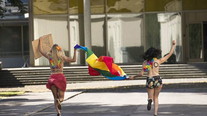 Two topless Femen activists who climed over a fence into the Russian embassy grounds runs towards the embassy building in Stockholm, Sweden, on Thursday Aug. 1, 2013, during the Stockholm Pride week celebrations, to protest against the country's anti-gay bill and stigmatization of homosexuals. Two topless activists climbed over a fence into the Russian embassy in Stockholm to protest against the country's anti-gay bill and stigmatization of homosexuals. Police were called to the embassy Thursday morning to remove the activists, who are now suspected of trespassing. They were released after confessing to trespassing.(AP Photo/Scanpix Sweden/Jonas Ekstromer) ** SWEDEN OUT **