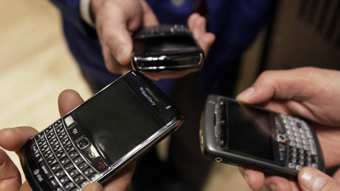 Three people on the floor of the New York Stock Exchange display their Blackberry smartphones, Wednesday, May 30, 2012. Research In Motion Ltd., the maker of the BlackBerry, is in steep decline. The company, once the crown jewel of the Canadian technology industry, is now worth 1 percent of Apple's market capitalization.  (AP Photo/Richard Drew)