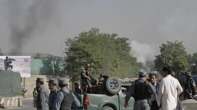 Afghan soldiers stand guard as smoke rises from the gate of the presidential palace in Kabul, Afghanistan, Tuesday June 25, 2013. The Taliban said they have hit one of the most secure areas of the Afghan capital with a suicide attack, as a series of explosions rocked the gate leading into the presidential palace. (AP Photo/Ahmad Jamshid)