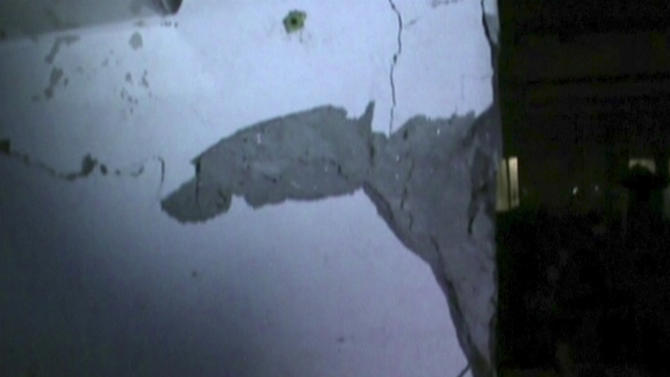 In this image made from Channel 1 video via AP video,  cracks are seen on the wall inside Rana Plaza building, as police investigated the building Tuesday, April 23, 2013,  one day before its collapse in Savar, Bangladesh.  The footage emerged on Friday, April 26,  of police in Dhaka visiting the Rana Plaza building in the city's Savar suburb to investigate cracks in its infrastructure - a day before the collapse of the structure killed hundreds of garment workers. Dhaka police say the cracks led them to order the building to be evacuated, but that the factories ignored the order.  (AP Photo/AP video) BANGLADESH OUT