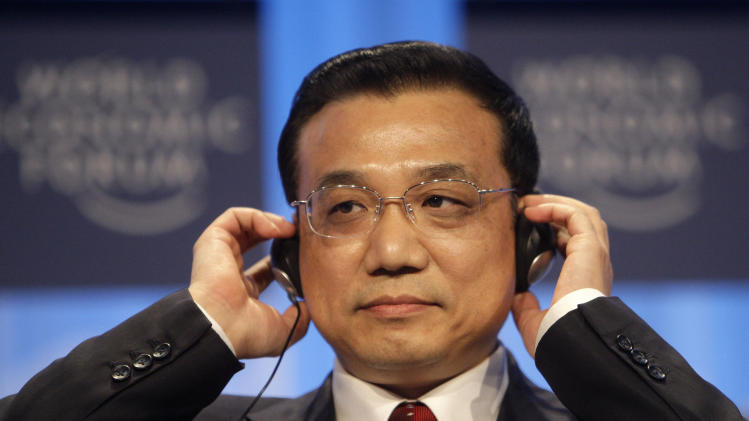 FILE - In this file photo taken Thursday, Jan. 28, 2010, Li Keqiang, Chinese vice premier, adjusts his headphones before addressing the World Economic Forum in Davos, Switzerland.  In line to take over Chinese Premier and oversee China's massive but rapidly slowing economy for the coming decade, Li speaks English and comes from a generation of politicians schooled during a time of greater openness to liberal Western ideas than their predecessors. (AP Photo/Anja Niedringhaus, File)