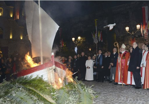 Prince Albert II of Monaco and Archbishop Barsi stand with members of the church as they watch a small fisherman's boat burn during the traditional Sainte Devote celebration in Monaco