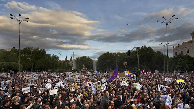 Protestors gather near Parliament demonstrating against austerity measures announced by the Spanish government in Madrid, Spain, Saturday, Sept. 29, 2012. Tens of thousands of Spaniards and Portuguese rallied in the streets to protest enduring deep economic pain from austerity cuts. In Madrid, demonstrators approached parliament for the third time this week to vent their anger against tax hikes, government spending cuts and the highest unemployment rate among the 17 nations that use the euro. (AP Photo/Daniel Ochoa De Olza)