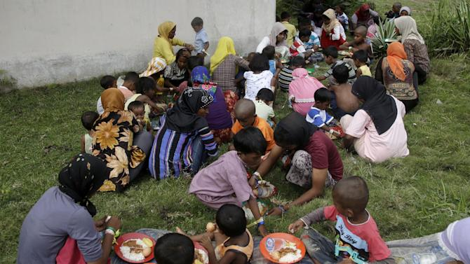 In this Saturday, May 23, 2015, photo, Ethnic Rohingya women and kids gather to eat at a temporary shelter in Bayeun, Aceh province, Indonesia. Thousands of migrants have washed ashore in Indonesia, Malaysia and Thailand since May 10, and thousands more are believed to be trapped at sea. The United Nations has warned that time is running out to save them. (AP Photo/Tatan Syuflana)
