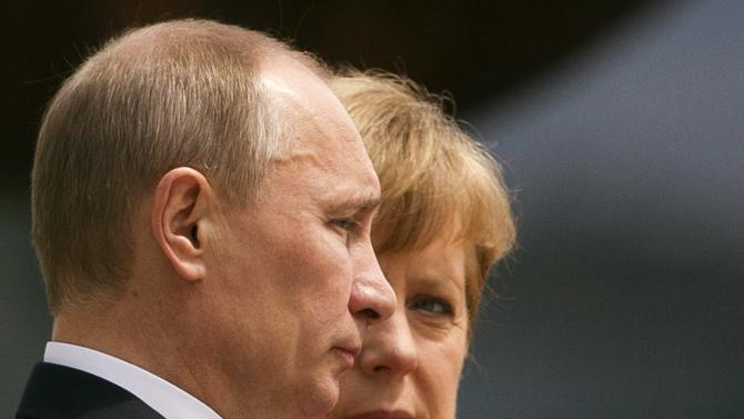 File photo shows German Chancellor Merkel and Russian President Putin listening to their national anthems before talks at Chancellery in Berlin