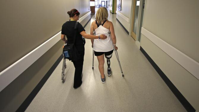 Boston Marathon bombing survivor Roseann Sdoia, of Boston, walks down a long corridor as she is followed by her physical therapist Dara Casparian at the Spaulding Rehabilitation Hospital, Friday June 20, 2013, in Boston. Sdoia went back to the hospital to learn to walk with her new leg. (AP Photo/Charles Krupa)