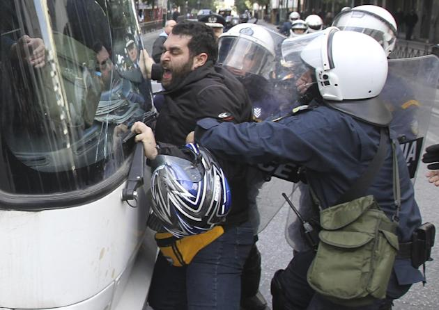 A man tries to stop the bus from driving away carrying detained protesters as riot police pull him away, during a protest outside the Labor Ministry in Athens, Wednesday, Jan. 30, 2013. Protesters fro