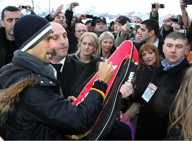 Tennis world number one Novak Djokovic signs autographs for fans on February 9, 2012, in the central Serbian town of Jagodina.  Novak Djokovic attended a ceremony reviling his wax sculpture in the Wax