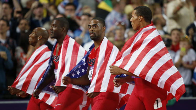 From left, United States' 4x100-meter relay team Trell Kimmons, Justin Gatlin, Tyson Gay and Ryan Bailey walk on the track taking the silver medal during the athletics in the Olympic Stadium at the 2012 Summer Olympics, London, Saturday, Aug. 11, 2012. (AP Photo/Matt Dunham)