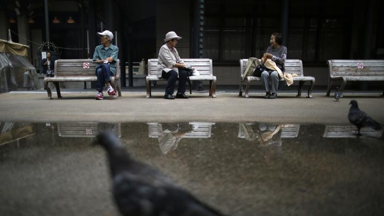 Elderly people take a break on bench seats at Tokyo's Sugamo district, an area popular among the Japanese elderly, in Tokyo