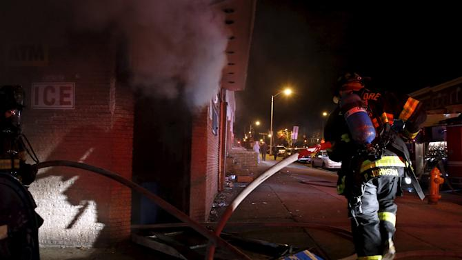 A Baltimore firefighter rushes into a fire in a burning building set ablaze by rioters during clashes in Baltimore