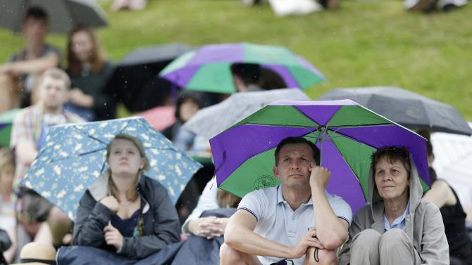 Spectators shield from the rain with umbrellas on 'Murray Mound' at the Wimbledon Tennis Championships in London
