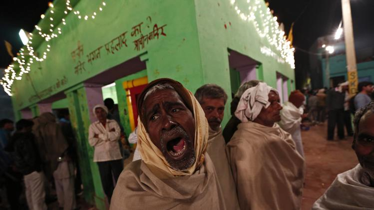 A villager yawns as he waits for Hindu priest Babulal to exit a temple and walk through a bonfire at Phalen village