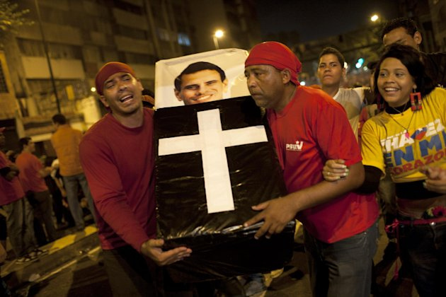 Supporters of Venezuela&#39;s President Hugo Chavez perform a mock funeral for opposition candidate Henrique Capriles as they celebrate in downtown Caracas, Venezuela, Sunday, Oct. 7, 2012. Chavez won re-election and a new endorsement of his socialist project Sunday, surviving his closest race yet after a bitter campaign against Capriles.(AP Photo/Ariana Cubillos)