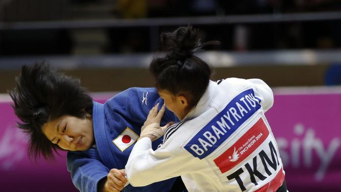 Japan's Misato Nakamura competes with Turkmenistan's Gulbadam Babamuratova during their -52kg women's judo final at the 17th Asian Games in Incheon