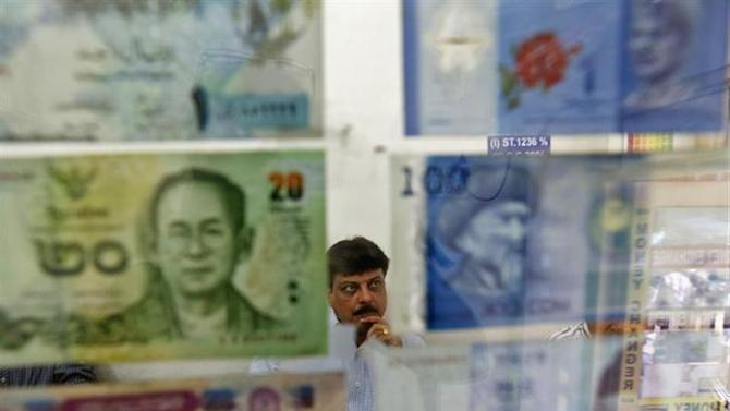 A man watches television inside his currency exchange shop in New Delhi August 30, 2013. REUTERS/Mansi Thapliyal/Files