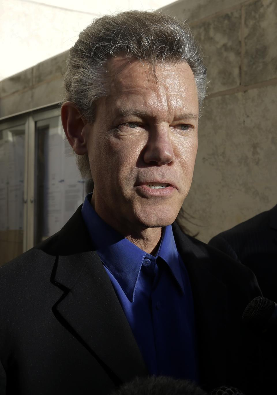 FILE - In this Jan. 31, 2013 file photo, country star Randy Travis makes comments after exiting the Grayson County Courthouse, in Sherman, Texas. Travis has filed a lawsuit to prevent two state agencies from releasing a patrol car video of his 2012 DWI arrest in North Texas. (AP Photo/Tony Gutierrez, File)