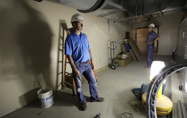 In this Tuesday, June 19, 2012 photo, electrical contractor Howie Drees inspects some newly-installed equipment on a job site in Carroll, Iowa. Drees, a third-generation contractor, gauges prosperity by his crowded work calendar. These days, he's so busy with mechanical and electrical projects he's hired an outside company to help and is searching for skilled workers. (AP Photo/Charlie Neibergall)