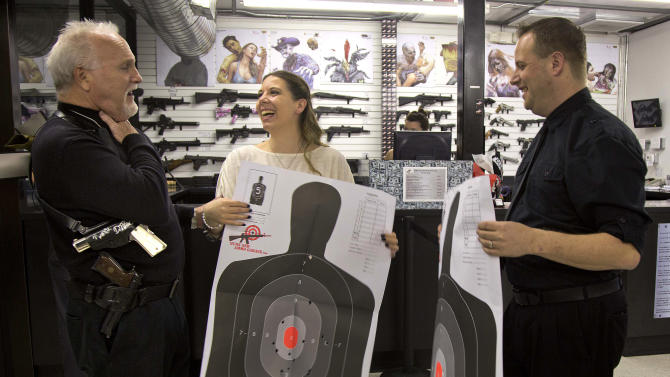 "Rev. ""Jimmy Mac"" McNamara, also known as the Pistol Packing Preacher, talks with Tanya, center, and Ted Morris, right, after the two took their wedding vows from him and then fired guns on the shooting range at the Guns and Ammo Garage, Thursday, Feb. 14, 2013, in Las Vegas.   The shooting range and gun store offered free vow renewals and wedding ceremonies by McNamara throughout the day on Thursday. (AP Photo/Julie Jacobson)"