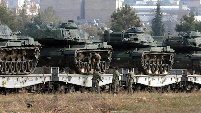 Turkish soldiers check tanks stationed at the train station after their arrival from western Turkey, in Gaziantep, Turkey, Friday, Nov. 27, 2015. Turkey shot down the Russian Su-24 bomber at the Syrian border on Tuesday, insisting it had violated its airspace despite repeated warnings. The tanks are expected to be deployed to the border with Syria.(DHA agency via AP) TURKEY OUT