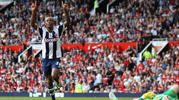 West Bromwich Albion's Saido Berahino celebrates scoring the 2nd goal against Manchester United while David De Gea lies flat out.
