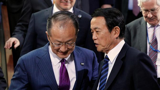 Japan's Finance Minister Taro Aso, right, talks to World Bank President Jim Yong Kim before the International Monetary Fund (IMF) family photo during the World Bank IMF Spring Meetings in Washington Saturday, April 20, 2013. (AP Photo/Molly Riley)