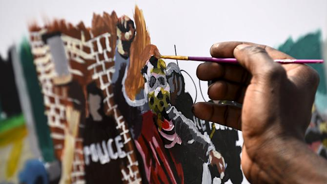 Kelvin Morris works on a painting depicting the Freddie Gray protests based on news photographs in front of the City Hall in Baltimore