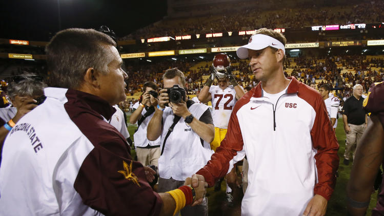In this Sept. 28, 2013 photo, Arizona State University head coach Todd Graham, left, shakes hands with USC head coach Lane Kiffin after ASU defeated USC 62-41 at Sun Devil Stadium in Tempe, Ariz. USC fired Kiffin early Sunday morning, not long after the team lost 62-41 at Arizona State. (AP Photo/The Arizona Republic, Rob Schumacher) MARICOPA COUNTY OUT. NO SALES