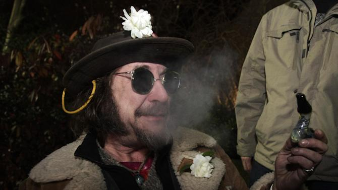 """A man known as """"Professor Gizmo,"""" smokes marijuana in a glass pipe, Wednesday, Dec. 5, 2012, just before midnight at the Space Needle in Seattle. Possession of marijuana became legal in Washington state at midnight, and several hundred people gathered at the Space Needle to smoke and celebrate the occasion, even though the new law does prohibit public use of marijuana. (AP Photo/Ted S. Warren)"""