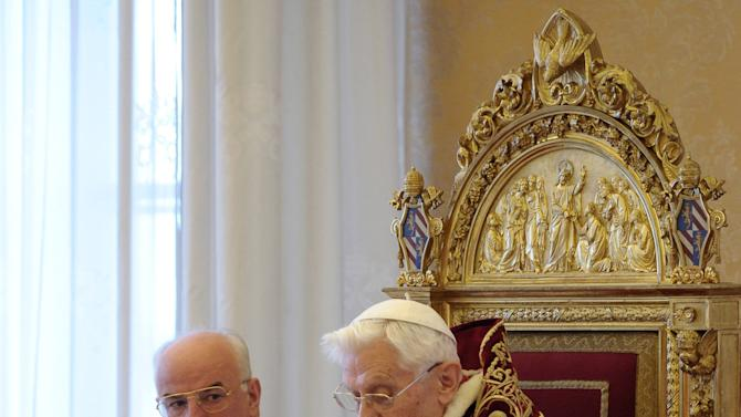 RECROP OF VAT114 - In this photo provided by the Vatican newspaper L'Osservatore Romano, Mons. Franco Comaldo, a pope aide, left, looks at Pope Benedict XVI as he reads a document in Latin where he announces his resignation, during a meeting of Vatican cardinals, at the Vatican, Monday, Feb. 11, 2013. Benedict XVI announced Monday that he would resign Feb. 28 - the first pontiff to do so in nearly 600 years. The decision sets the stage for a conclave to elect a new pope before the end of March. (AP Photo/L'Osservatore Romano, ho)