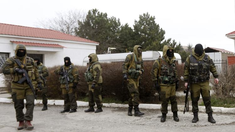 Armed men, believed to be Russian servicemen, stand at the entrance of a military unit in Simferopol