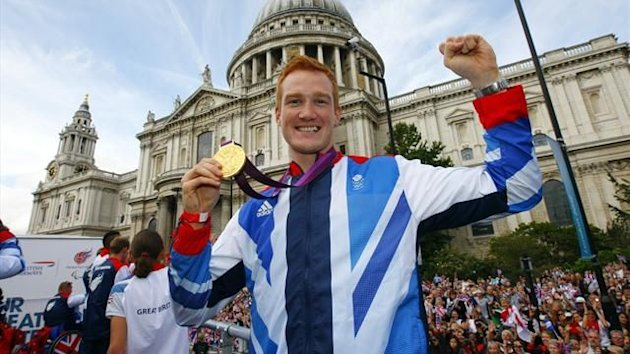 Athlete Greg Rutherford holds his long jump gold medal during a parade as it passes St Paul's Cathedral in the City of London