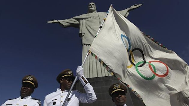 "Municipal Guards hold up the Olympic Flag in front of ""Christ the Redeemer"" statue during a blessing ceremony in Rio de Janeiro (Reuters)"