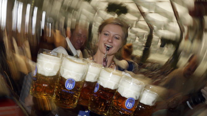 "A waitress carries beer mugs in the Hofbraeuhaus tent after the opening of the famous Bavarian ""Oktoberfest"" beer festival in Munich, southern Germany, Saturday, Sept. 22, 2012.  The world's largest beer festival, to be held from Sept. 22 to Oct. 7, 2012, will see some million visitors. (AP Photo/Matthias Schrader) EDS NOTE - SHUTTER SPEED CAUSING BLUR"