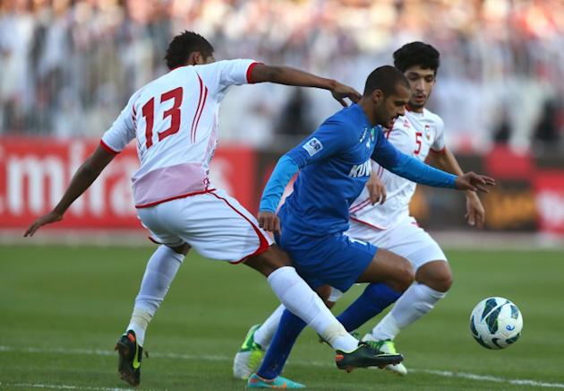 Bader al-Motawaa (C) of Kuwait vies for the ball against Khamis Ismail (L) and Amer Abdelrahman (R) of the United Arab Emirates during the two teams' semi final match in the 21st Gulf Cup in Manama, o
