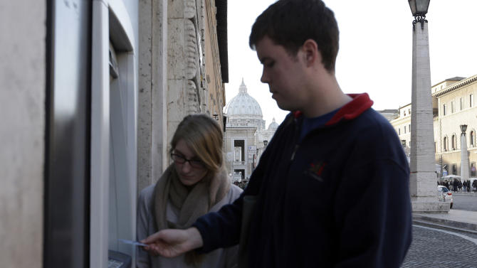 """Ben Kiniry, of Texas, gets cash from an ATM machine along Rome's Via della Conciliazione, the main road leading to the Vatican St. Peter's Basilica, whose dome is visible in background, Thursday, Jan. 3, 2013. It's """"cash only"""" now for tourists at the Vatican wanting to pay for museum tickets, souvenirs and other services after Italy's central bank decided to block electronic payments, including credit cards, at the tiny city state. The Italian daily Corriere della Sera reported Thursday that Bank of Italy took the action because the Holy See has not yet fully complied with European Union safeguards against money laundering. That means Italian banks are not authorized to operate within the Vatican, which is in the process of improving its mechanisms to combat laundering. The Vatican says it's scrambling to find a non-Italian bank to provide the electronic payment services """"quite soon"""" but declined to discuss Bank of Italy's concerns. The central bank had no immediate comment on the situation. (AP Photo/Alessandra Tarantino)"""