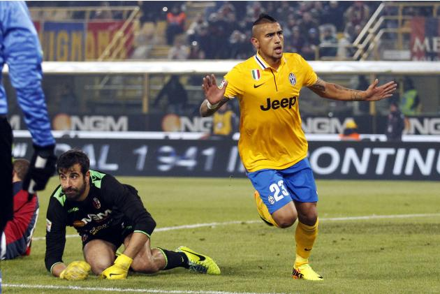 Juventus' Vidal celebrates after scoring as Bologna's Curci kneels on the field during their Italian Serie A soccer match at the Dall'Ara stadium in Bologna