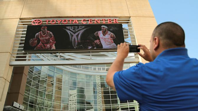 Houston Rockets fan Frank Vasquez takes a photograph of free agent forward Carmelo Anthony wearing Rockets jerseys in composite images on the Toyota Center marquee on Wednesday, July 2, 2014, in Houston. Anthony was wearing his No. 7 in both renderings, despite the fact that current Rocket Jeremy Lin wears that number. The Rockets would likely have to unload the point guard to snag Anthony